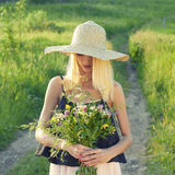 Country girl in hat with flowers Stock Photography