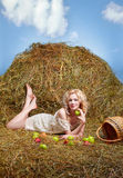 Country girl on hay. Portrait of beautiful blonde country girl posing laying on yellow hay with apples spilled from basket Stock Images