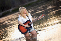 Country Girl Playing Acoustic Guitar in River Stock Image