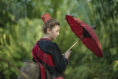 Country girl. Portrait holding a red umbrella in outdoors,beautiful happy Asian girl smile and laugh together Royalty Free Stock Images