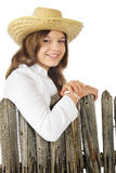 Country Girl Portriat. Head and shoulders portrait of a beautiful young teen in a straw hat  leaning on a weathered picket fence Stock Photo