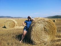Country girl posing in hayfield Royalty Free Stock Photo
