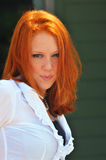 Country girl red head. Tan red hair country girl in white shirt and freckles with green eyes. Sunlight shining on her hair Stock Image