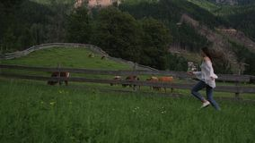 Country girl is running in farm in Alpine meadows with cows pasture