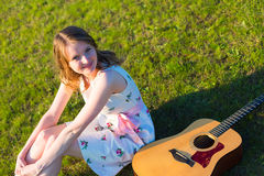 Country  girl sitting with acoustic guitar at field Royalty Free Stock Images