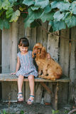 Country girl sitting on a bench with her dog under vine. wooden Stock Photo