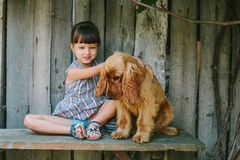 Country girl sitting on a bench with her dog under vine. wooden Royalty Free Stock Image