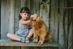 Country girl sitting on a bench with her dog under vine. wooden Stock Image