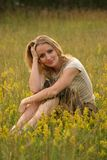 Country girl sitting in the grass royalty free stock photos