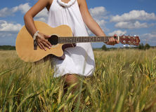 Country girl sitting with guitar. At wheat field Stock Photo