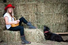 Country girl sitting on hay bale with her dog Royalty Free Stock Images