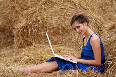 Country girl sitting on hay with laptop Royalty Free Stock Image