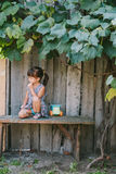 Country girl sitting  under vine. girl playing with her toy. Royalty Free Stock Photo