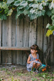 Country girl sitting  under vine. girl playing with her toy. Stock Photo