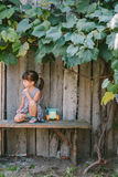 Country girl sitting  under vine. girl playing with her toy. Royalty Free Stock Photos