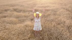 Country girl standing in a field, sends a kiss.The camera shoots up, aerial view. Smiling beautiful young girl sends a kiss to the camera moving away and waving stock video footage
