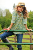 Country Girl Wearing Straw Fedora. A young smiling country girl with long hair wearing a straw hat and farm boots standing on a cattle gate Stock Images