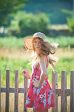 Country girl. Young redhead girl in country style outfit, standing over wooden fence Stock Photos