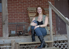 Country girl. A young woman with red hear, wearing blue jeans, a vest and black sleeveless shirt, sitting on an old porch outside a warehouse Royalty Free Stock Photos