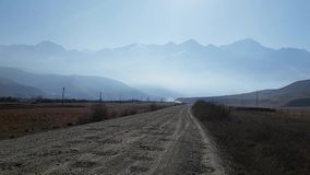 Country gravel road. Panoramic view of the mountains in the haze. Morning autumn landscape in the Caucasus mountains. stock video footage