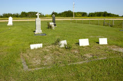 Country Graveyard. Small graveyard with four white stones with no inscription in the foreground Stock Image
