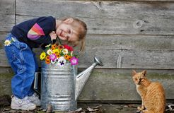 little girl with flowers and cat Royalty Free Stock Image