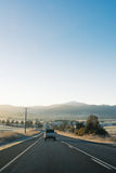 Country highway with cars leading towards mountains at sunrise. Cars driving down a country highway in the early morning as the sun rises casting a warm glow Royalty Free Stock Photo