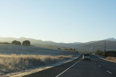 Country highway with cars leading towards mountains at sunrise. Cars driving down a country highway in the early morning as the sun rises casting a warm glow Stock Photo