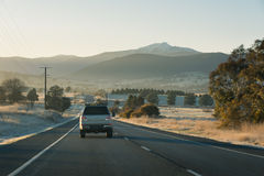 Country highway with cars leading towards mountains at sunrise. Cars driving down a country highway in the early morning as the sun rises casting a warm glow Stock Photos