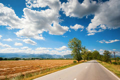 A country highway under a bright blue sky Stock Photo