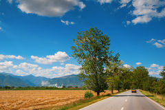 A country highway under a bright blue sky Stock Image