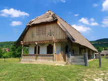 Country home from 1900. Wooden country house with roof made of straw in the middle of green fields and hills. Blue sky and clouds Royalty Free Stock Photo