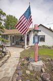 Country home with an Uncle Sam wood carving and American flag Royalty Free Stock Photography