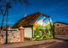 Country house with colorful graffiti. Casecow, Germany - March 8, 2014: Country house with colorful graffiti.This graffiti shows a green frog in the grass Royalty Free Stock Image