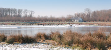 Country house on the edge of a lake with a thin layer of ice Stock Images