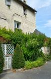Country house in France. Country stone built house with green shrubs and plants in front and white gates Stock Photo