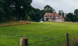 Country house with green garden and lawn in the region of Normandy, France. Beautiful countryside, french lifestyle and Royalty Free Stock Photography