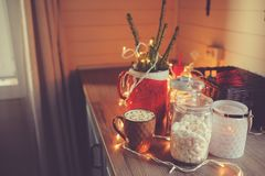 Country house kitchen decorated for Christmas and new year Holidays. Marhmallows, candles, cocoa and nuts in modern jars Stock Photography