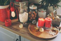 Country house kitchen decorated for Christmas and new year Holidays. Marhmallows, candles, cocoa and nuts in modern jars Stock Images