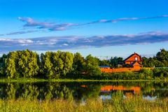 Country house by the pond. At sunset Royalty Free Stock Photos