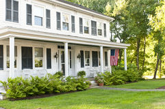 Country house porch. Comfortable country house with porch, landscaping and flag Royalty Free Stock Photo