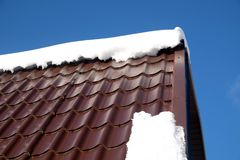 Country house roof from brown metal tile with snow in sunny spring day under blue sky with white clouds. Side of country house roof from brown metal tile with Royalty Free Stock Photos