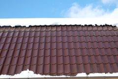 Country house roof from brown metal tile with snow in sunny spring day under blue sky with white clouds. Side of country house roof from brown metal tile with Royalty Free Stock Photography