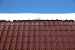 Free Country House Roof From Brown Metal Tile With Snow In Sunny Spring Day Under Blue Sky Stock Image - 112142041