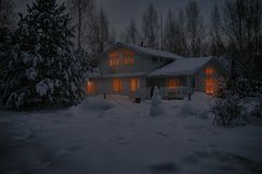 Country house in snowy cold winter night with lighted windows on Christmas Eve. Country house covered with snow in cold winter night with lighted windows on royalty free stock images