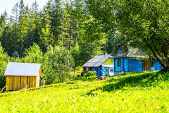 Country houses on a hill. By the forest in ukrainian village. Yard with green grass and stall Stock Photos