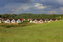Country houses in the meadow near the forest Royalty Free Stock Photography