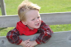 Country Kid. Young Boy with red bandana around neck and flannel shirt, leaning through fence royalty free stock images