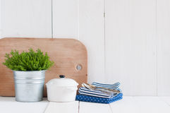 Country kitchen decoration. Cottage life, country kitchen decoration: a house plant in a metal pot, kitchen pottery, utensils and napkins on white painted board Royalty Free Stock Photography