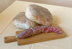 Country kitchen, rustic bread and salami on board. Authentic. Br Royalty Free Stock Images